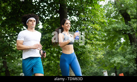 Happy young people jogging and exercising in nature - Stock Image