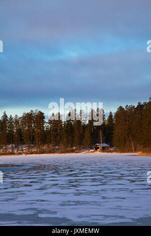 Boathouse at a frozen forest lake in early winter. - Stock Image