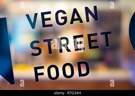 vegan street food black text on the bar window in Warsaw, Poland - Stock Image