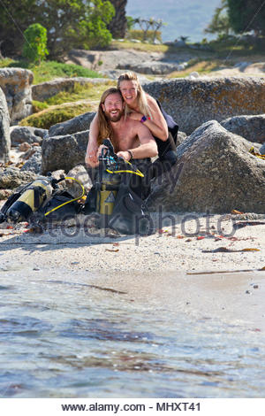 Couple preparing scuba equipment for a dive from the beach and smiling at camera - Stock Image