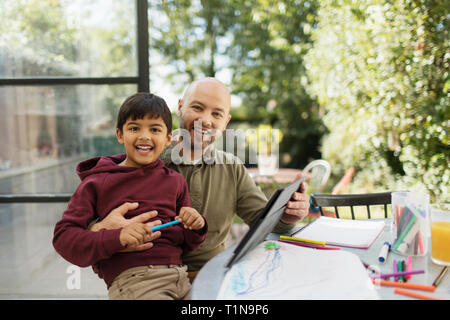 Portrait happy father and son coloring and using digital tablet at table - Stock Image