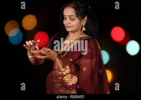 A beautiful Indian woman busy adjusting the flame of the traditional lamp during Diwali festival in India, on the backdrop of blur colorful decorative - Stock Image