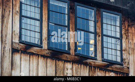 Weathered wooden leaded glass window on a wooden fronted house in Bruges which overlooks the canal's waterway - Stock Image