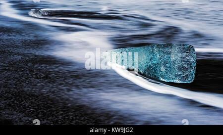 Iceberg on Black Sand - Stock Image