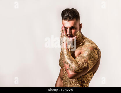 Muscular naked man covered with golden ing chin and looking down sensually on black background - Stock Image