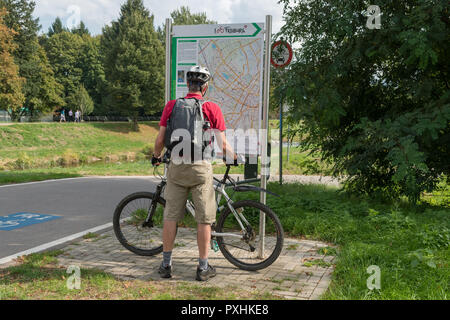 Freiburg im Breisgau cycling and cycle lanes - male cyclist checking route map, Freiburg, Baden-Wurttemberg, Germany, Europe - Stock Image