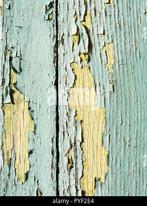 Faded and peeling paintwork on window shutter - France. - Stock Image