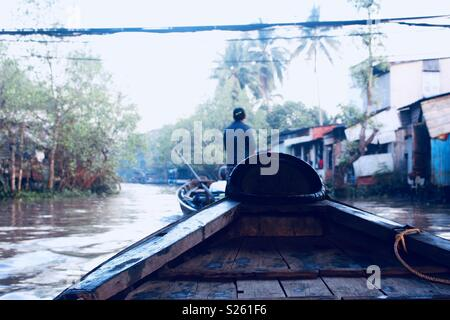 View from end of a wooden boat sailing through the Mekong Delta, Vietnam - Stock Image