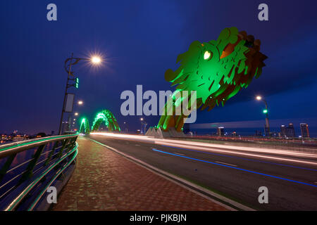 Long exposure of Dragon Bridge at night in Da Nang, Vietnam, with car headlight light trails. The dragon's head spews out flames and sprays of water e - Stock Image
