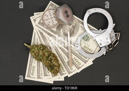 Closeup of marijuana bud joint and metal grinder with dirty money as illegal drug concept isolated on black - Stock Image