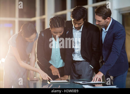 Group of businesspeople discussing together over digital tablet - Stock Image