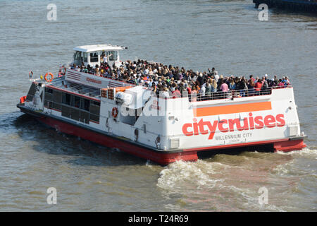 The upper deck of a packed CityCruises tourist cruise boat on the River Thames in London, UK - Stock Image