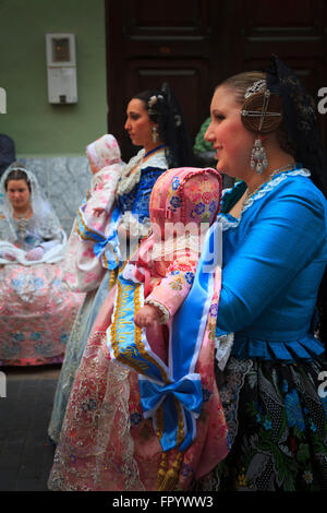 Two women in traditional Spanish Costume carrying babies in the procession of the Fallas Festival in Gandia Spain - Stock Image