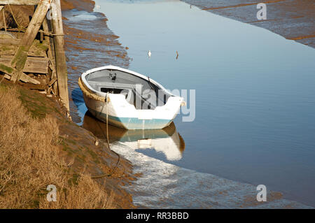 A small white dinghy beached at low tide in the base of a creek on the North Norfolk coast at Thornham, Norfolk, England, United Kingdom, Europe. - Stock Image