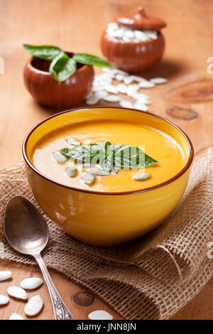 Vegetable soup puree with pumpkin seeds in white bowl on wooden background - Stock Image