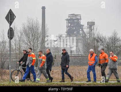22 March 2019, Brandenburg, Eisenhüttenstadt: Employees of the steel company Arcelor Mittal Eisenhüttenstadt GmbH go to a public works meeting. The city of Eisenhüttenstadt and the staff of Arcelor Mittal are concerned about maintaining their steel location. More than 1000 employees attended the works meeting early on Friday morning. Photo: Patrick Pleul/dpa-Zentralbild/dpa - Stock Image