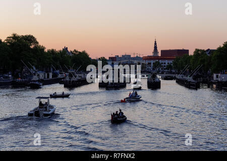 Boats on the river Amstel at sunset, Amsterdam, Netherlands - Stock Image