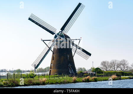 Traditional Dutch wind mill built along canal in North Holland, spring landscape - Stock Image
