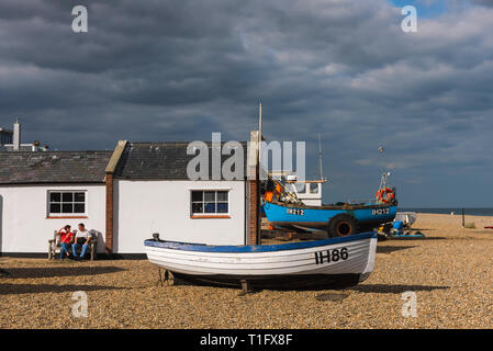 Aldeburgh beach Suffolk, view of a middle aged couple relaxing beside fishing boats on the beach at Aldeburgh, Suffolk, England, UK. - Stock Image