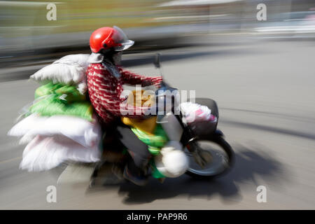 Panning photo of motion blurred moped rider carrying bags in the streets of Hanoi, Vietnam. - Stock Image