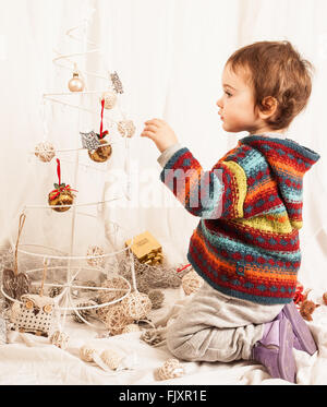 Boy Playing With Christmas Decoration On Bed At Home - Stock Image