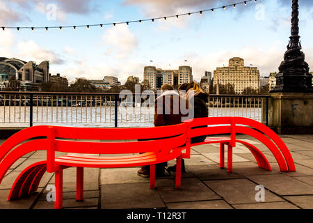 A young couple sit on a bright red bench on the South Bank of the Thames with a view of famous London landmark buildings including The Adelphi - Stock Image