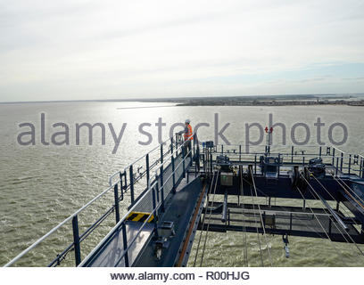 Dock supervisor at the end of crane above cargo ship and container looking out to sea - Stock Image