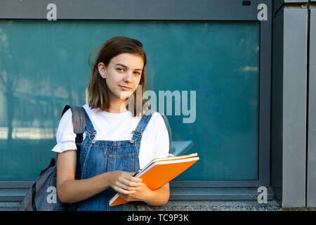 Portrait of a beautiful student girl leaning against the window of the school - Stock Image