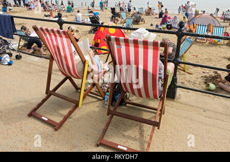People relaxing in deckchairs on the seafront at Scarborough. - Stock Image