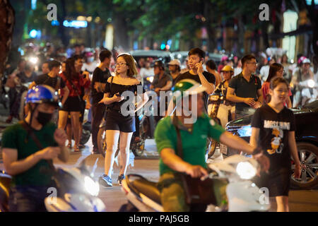 Motion blurred night shot of pedestrians trying to cross road full of mopeds in busy street in Hanoi, Vietnam. The seemingly chaotic traffic scares to - Stock Image