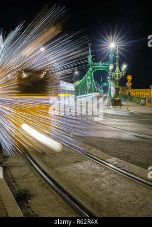 Budapest, Hungary - Festively decorated light tram (Fenyvillamos) on the move at Liberty Bridge (Szabadsag hid) by night. Christmas season in Budapest - Stock Image