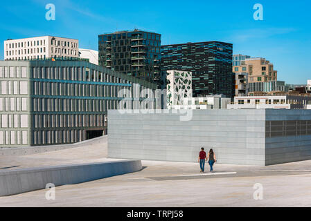 Man woman city, rear view of a young couple walking alone through an urban environment in the Barcode area of Oslo, Norway. - Stock Image