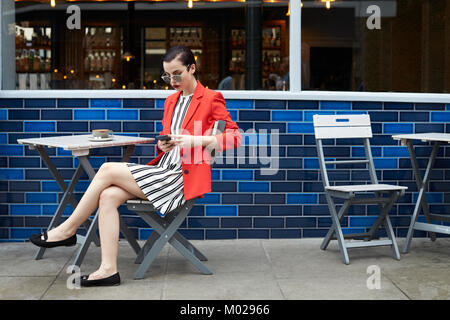 Woman sitting outside a cafe using smartphone, side view - Stock Image