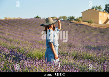 The beautiful young girl in a blue dress and hat walks across the field of a lavender, long curly hair, smile, pleasure, sunglasses - Stock Image