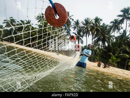 A fisherman pulls in his catch on a beach in Sierra Leone's Turtle Islands. - Stock Image