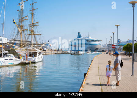 Father daughter, rear view of a father and daughter holding hands on the quayside in Tallinn harbor looking at boats and ships, Estonia. - Stock Image