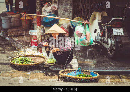 A street vendor weighs up some produce on a street in Hanoi's Old Quarter - Stock Image