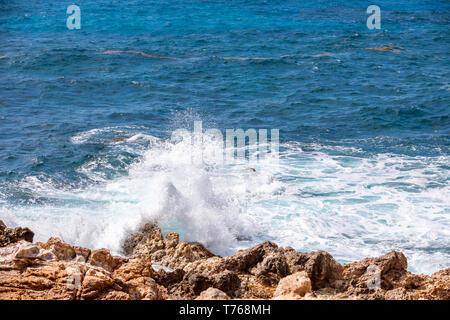 ocean waves crashing on the rocky coast of Grand Fond, St Barts - Stock Image