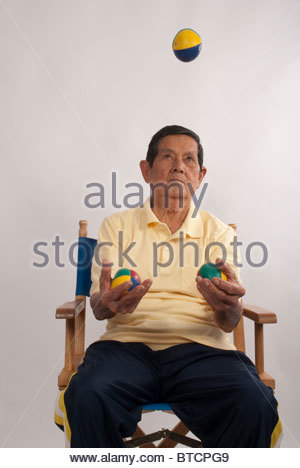 Elderly man practices juggling. - Stock Image