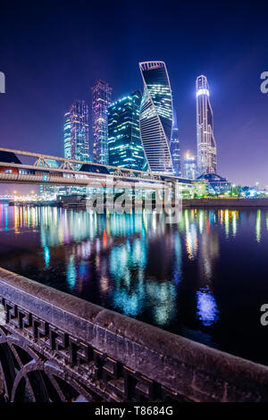 Night view of the skyscrapers of Moscow-City from the embankment across the river - Stock Image