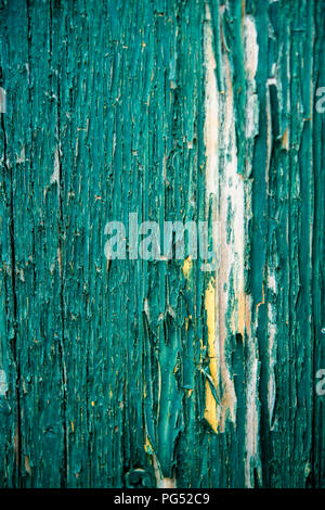 Detail of cracked and peeling green paint on an old wooden fence - Stock Image