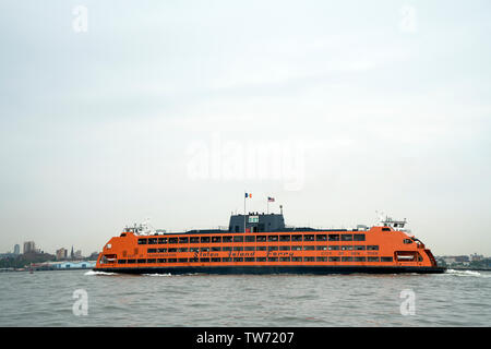 With Brooklyn in the background, the Staten Island ferry crossed New York harbor on its way from Staten Island to its South Ferry mooring in Manhattan - Stock Image