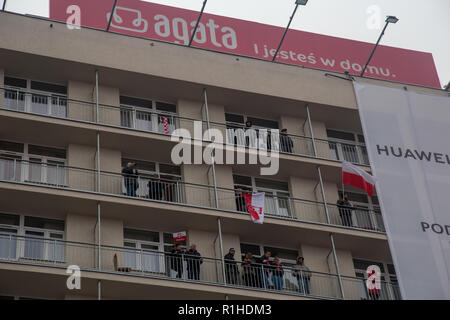 Warsaw, Poland, 11 November 2018: Celebrations of Polish Independence Day: people with Polish flags and advertisement of Agata furniture shop - Stock Image