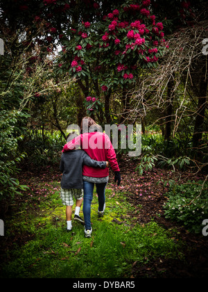 Mother and son walking in park - Stock Image