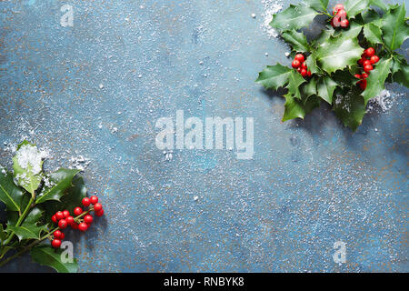 Christmas background with real holly leaves and red berries on a blue stone background covered in snow with copy space. - Stock Image