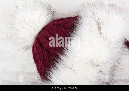 Red knitted winter hat with fur on white wooden background. - Stock Image