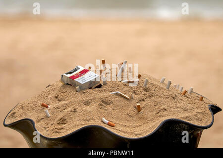 Cigarette butts discarded and stubbed out in a sand ashtray - Stock Image