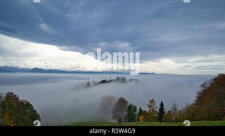 Above the clouds in the Swiss alps during autumn - Stock Image