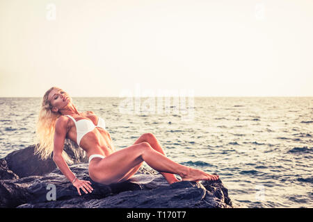 Blonde fitness model pose on the rocks with ocean in background - beautiful babe and nature concept for vacation and body results concept - Stock Image