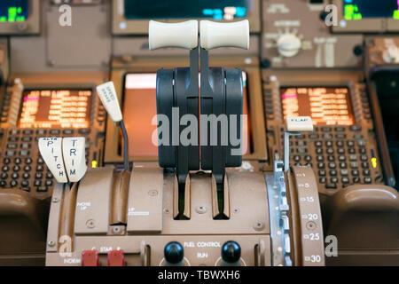 Engines thrust levers inside a big jet plane cockpit. - Stock Image